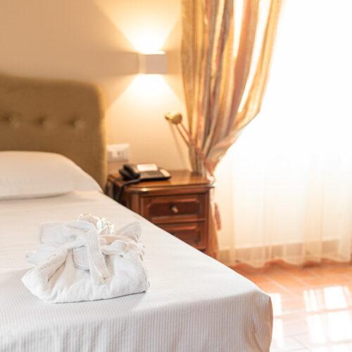 Junior suite - Dettaglio letto con finestra, accappatoio e ciabattine di cortesia